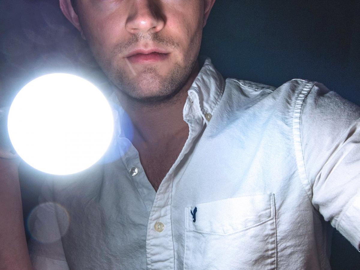 Man holding a bright flashlight
